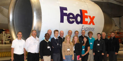 Group photo of student group in front of a FedEx plane